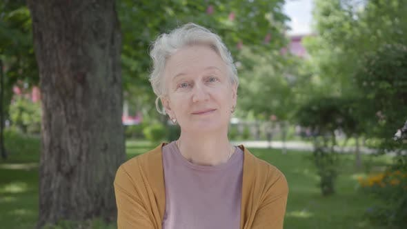 Thumbnail for Portrait of Cute Old Woman with Grey Hair Smiling in the Green Amazing Park