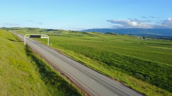 Thumbnail for Beautiful Aerial Background Shot of Highway Going Through Peaceful Grassland Hills and Distant