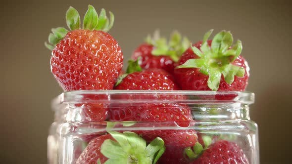 Thumbnail for Rotating Glass Jar Full Of Vibrant Red Strawberry Fruit With Brown Background