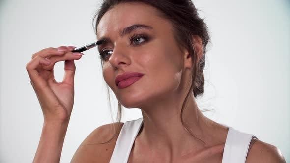 Augenbrauen Makeup. Frau kämmt Augenbraue mit Pinsel-Nahaufnahme