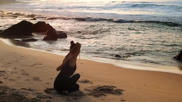 Thumbnail for Young Beautiful Woman Stretches Doing Yoga Against Ocean