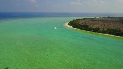 Wide angle aerial abstract shot of a white sandy paradise beach and blue sea background in vibrant 4