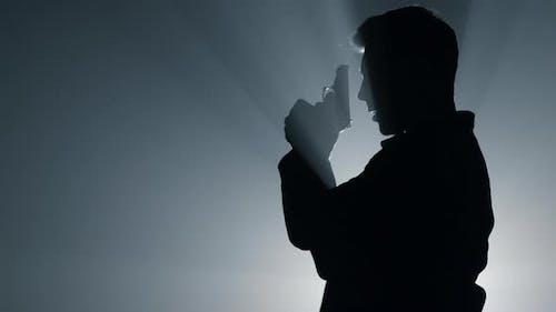Silhouette Täter schießt Pistole in Dunkelheit
