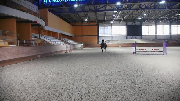 Equestrian Sports  a Woman in Black Clothes Galloping on the Empty Hippodrome Field