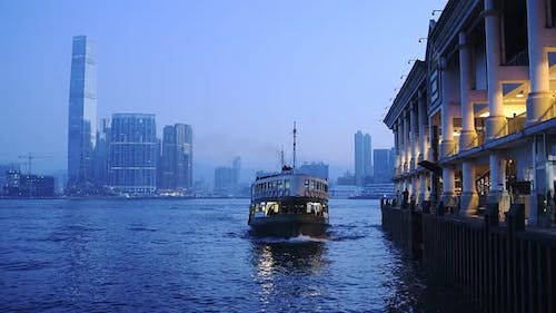 Star Ferry Boat Arriving At Kowloon Pier With Hong Kong Central Skyline On The Background At Night.