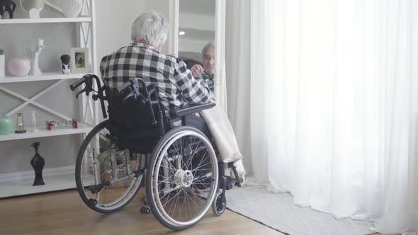 Thumbnail for Back View of Mature Caucasian Man in Wheelchair Looking at His Reflection in Mirror, Sad Elderly