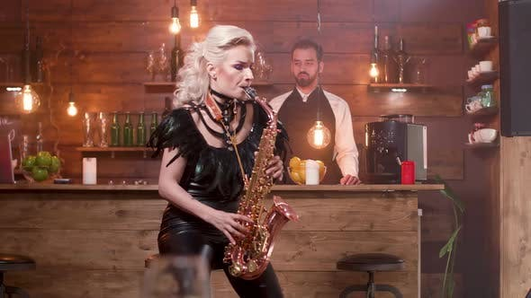 Thumbnail for Young Lady in Sexy Black Stage Costume Performs a Song on a Saxophone