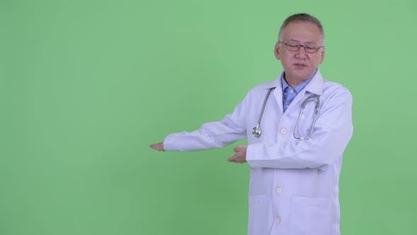 Thumbnail for Stressed Mature Japanese Man Doctor Presenting To the Back