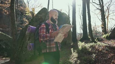 Stylish Hipster Man Traveler with Backpack Holding Map and Exploring on Top of Mountains