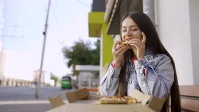 Portrait of a young woman eating pizza outdoors in the street