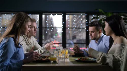 Young Mates Suppering, Conversating in Restaurant