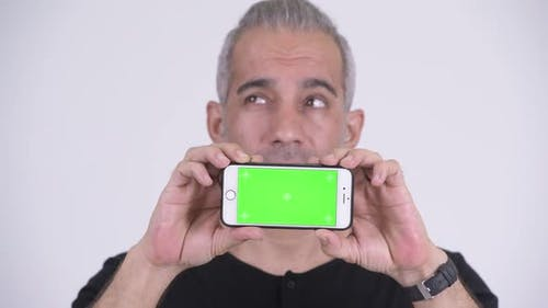 Happy Handsome Persian Man Thinking While Showing Phone