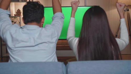 Back View Of Excited Asian Couple Watching Tv With Mock Up Green Screen Together Sitting On A Sofa