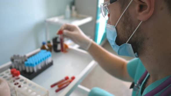 Thumbnail for Profile of Scientist Testing Test Tube with Blood Sample To Coronavirus. Young Laboratory Worker in