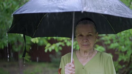 Sad Senior Woman Under Umbrella