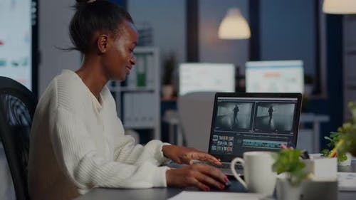 Black Delighted Videographer Editing Movie on Professional Laptop