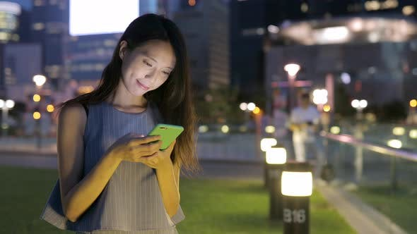 Thumbnail for Woman looking at mobile phone at evening
