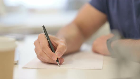 Close Up of Male Hands Writing on Paper