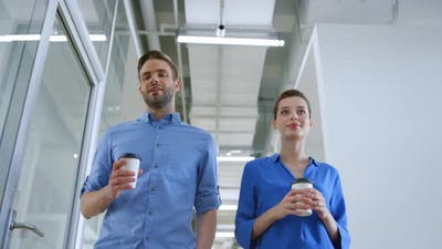 Colleagues Walking with Paper Cups in Office