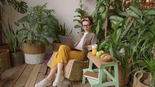 Young Woman Drinking from Eco-Friendly Cup and Working on Laptop at Home