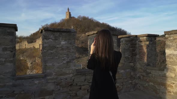 Brunette Girl with Black Jacket Enjoying Sunny Autumn Day in Old Medieval Stronghold Called