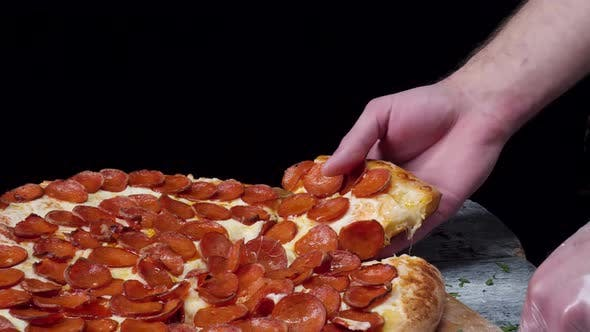 Pizza And Slice Of Pizza In Hand On The Table
