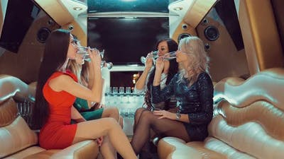 Girlfriends Clap Glasses and Drink in a Limousine