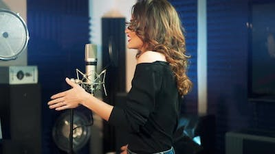 Half-length profile of a beautiful singer in the recording studio.
