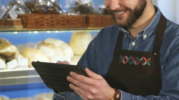 Thumbnail for Cropped Close Up of a Male Baker Using Digital Tablet Working at the Bakery