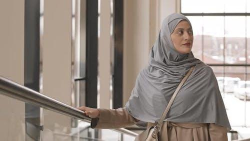 Arabic Woman Going Up Escalator in Modern Office