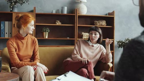 Mother and Daughter Having Consultation with Male Counselor