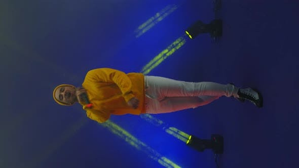Thumbnail for Vertical Video. A Singer in a Yellow Suit Dances and Sings with a Microphone in Neon Color. Jump and