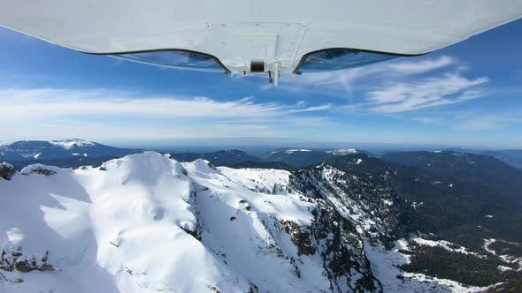 Cover Image for Snowy Cascade Mountains Aerial Flying View From Camera Mounted Under Helicopter Panoramic View