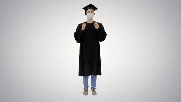 Thumbnail for Young Man with Graduation Gown in Medical Mask on Gradient Background