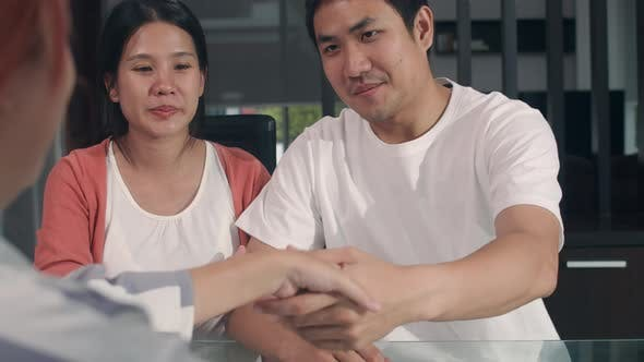 Young Asian Pregnant couple sign contract documents at home, Japanese consulting Buying new house