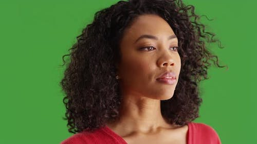 Close up of pretty black woman looking wistfully to the side on greenscreen