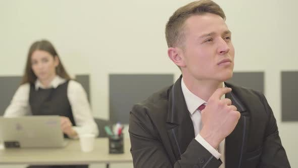 Thumbnail for Portrait Handsome Thoughtful Young Man Sitting in the Foreground in the Office While His Female