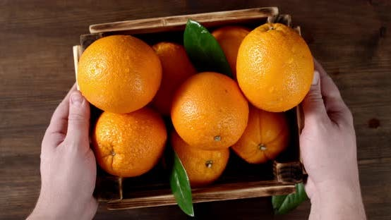 Hands Men Put Wooden Box with Fresh Orange on the Table.