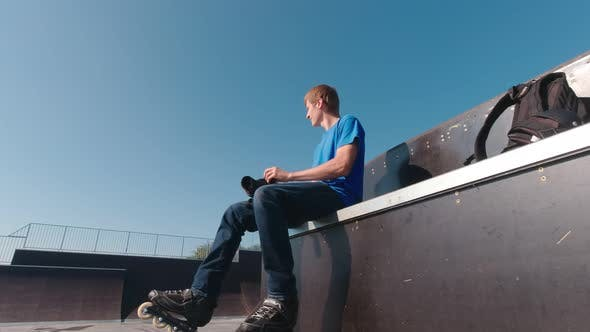 Man In Skate Park Putting On Protection
