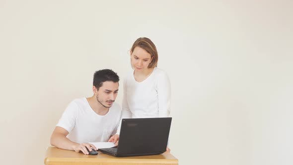 Unhappy Couple with Bills and Laptop at Home, Paying Taxes