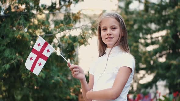 Thumbnail for Little Girl Holding Georgian Flag Standing Outside