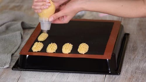 Pastry Chef with Confectionery Bag Squeezing Fresh Pastry Dough on Tray with Paper