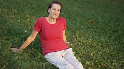 Elderly Woman Sitting on the Grass