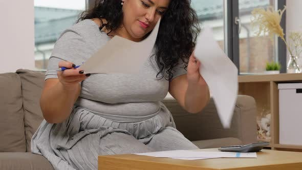 Thumbnail for Woman with Papers and Calculator at Home