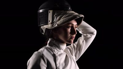 Side View of Young Woman Fencer Puts Sports Mask Helmet
