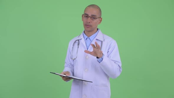 Thumbnail for Happy Bald Multi Ethnic Man Doctor Talking While Holding Clipboard
