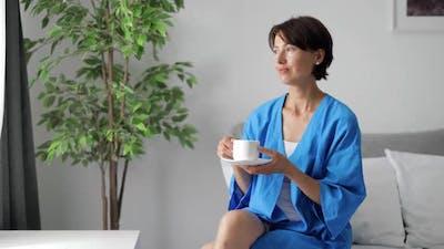 Woman Drinking Coffee in Bedroom