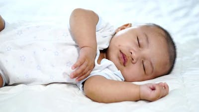 little baby sleeping on a bed at home