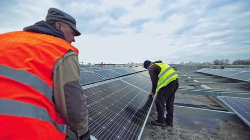 Workers attach photovoltaic panel