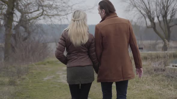 Thumbnail for Back View of Elegant Brunette Man and Blond Woman Strolling Outdoors and Talking. Happy Caucasian